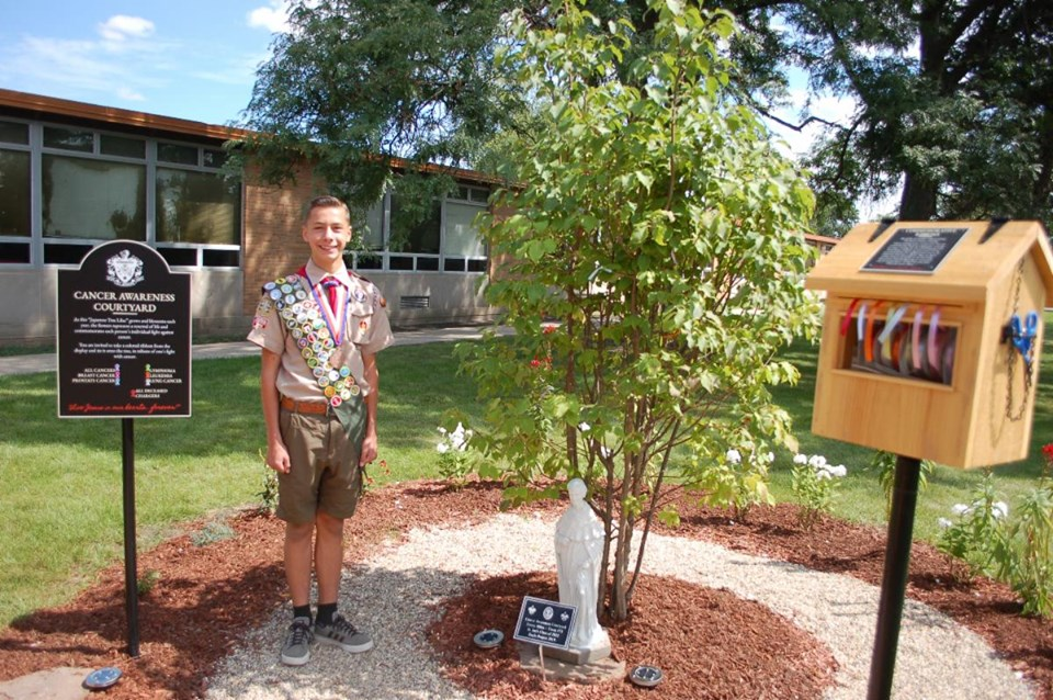 Sophomore Jimmy Milas poses next to the tree he planted as part of his Eagle Scout project in the East entryway at St. Joseph.